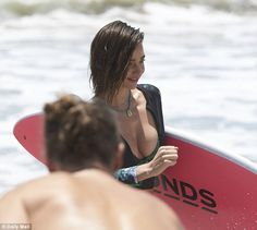 Surf's up: Miranda flashed some cleavage in a black and green floral bikini top and rash guard while holding a pink surfboard