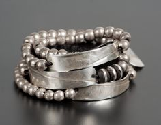 Round Bead & Rectangle Bracelet by John Siever. Wrap-around leather cord bracelet with three oxidized sterling silver metal strips and handcrafted silver-colored African beads. This bracelet can also be worn as a necklace. The patina on the beads may change with age.