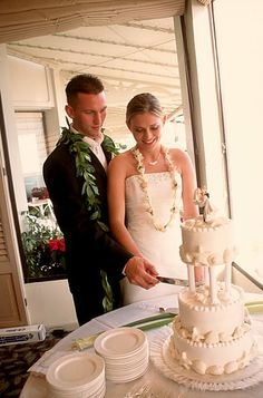 Wedding cake cutting photo of Erica and Matthew at Sheraton Moana Surfrider. Photography by Dream Weddings Hawaii
