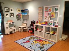 Family/Dining room turned into playroom. Pictures of our son with family members who live long distance hang above the play kitchen. The art corner provides storage area & highest shelf contains items only accessible to me & are used under my supervision (i.e. glue, scissors, play-doh). A white shelving unit is used in a lackadaisical Montessori-style with the top being open & the bottom containing blocks, Legos, matchbox cars, etc. Above it, a chicken-wire frame is used to display artwork.