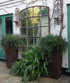 Neisha Crosland mirror with plants as focal point in garden
