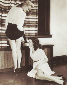 """Not quite sure what's going on here, but I'm guessing one is just helping the other with """"the straightening of the nylons,"""" a common practice in the 30's to the 60's...."""