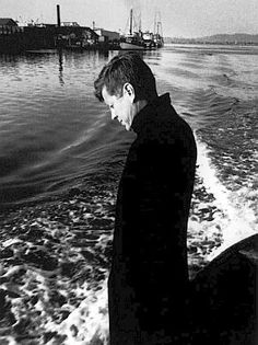 Nov. 1959: JFK in a quiet moment gazing into a tug boat's wake during a tour of Coos Bay, Oregon. (Jacques Lowe).
