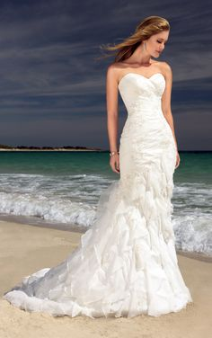 This mermaid style, wedding gown is a true go to design. With the nickname Five-0, it boasts a sweetheart neckline and is beautifully crafted with Soft Organza in wave-like tiers. The beaded lace appliques add a subtle pearly shimmer. This is not just a dress; it is the Ali`i of wedding gowns.