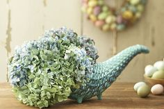 A piece of wet floral foam in the cornucopia and insert the hydrangea stems into the foam. Then, if you'd like, incorporate some decorative Easter eggs and seasonal fruits and veggies into the design. Just use your imagination and what you already have on hand!
