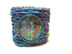 Plum and Teal Shibori Silk Cuff Bracelet with Dichroic Glass Cabochon by onthepondcreations on Etsy https://www.etsy.com/listing/262454624/plum-and-teal-shibori-silk-cuff-bracelet