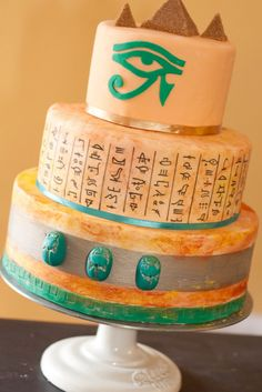 Egyptiona chocolate cake with white chocolate ganache.  Write hieroglyphics with an edible marker. Make pyramids out of brown sugar and hand-cut the Egyptian eye.