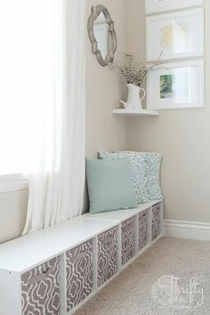 TA: make shift mud room idea; shelf turned on its side with fabric cubes against a paneled wall with hooks