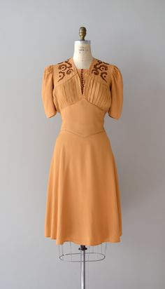 1930s rich butterscotch rayon dress with chocolate scroll embroidery on the yoke paneled shoulder and back of bodice, window pane plated bodice with button modestly panel (that snaps in), short puff shoulder sleeve, reverse yoked waist, and swingy skirt.