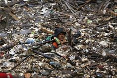 Un volontario alle prese con le montagne di rifiuti portate dalle alluvioni nel centro di Giacarta, Indonesia