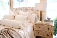 This look features an all white and cream bed with feminine pleats and lace. There are a lot of weathered, natural elements like the wooden lamp and the distressed cream side table. Overall, it's a neutral, classic look full of pretty details.
