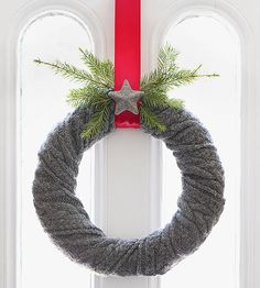 Four supplies and five minutes are all you need to make an adorable scarf wreath. Simply wrap a wool scarf around a foam or straw wreath form, pinning it in place as you go. Pin your final wrap and hang with ribbon. A sprig of spruce and cozy star decoration are optional add-ons./