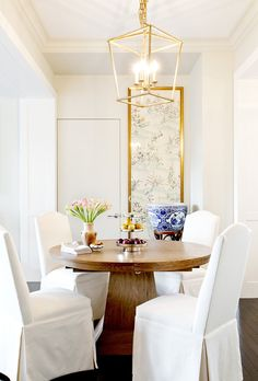 Wooden circular dining table with plush white linen chairs and gold hanging lantern light fixture