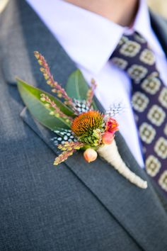 Feathers and budding flowers made up the groom's textured boutonniere. Boutonnieres, Rustic Boutonniere, Groomsmen Boutonniere, Groom And Groomsmen, Orange Boutonniere, Prom Flowers, Silk Flowers, Wedding Flowers, Bouquet Flowers