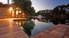 Pool with dark interior and infinity edge looking over a lake. Full decking around pool with built-in underground pool cover. Pinned to Pool Design by Darin Bradbury.