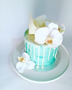 blue drip cake with flowers and chocolate sail
