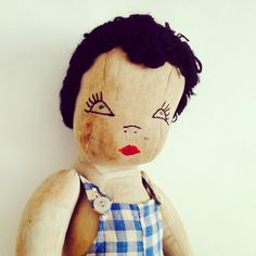 Old doll in gingham dungarees