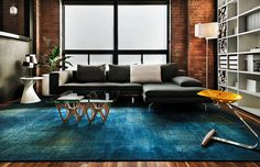 Contemporary living space with rug in copper blue and plush sofa in dark gray [From: James Maynard- Vantage Imagery]