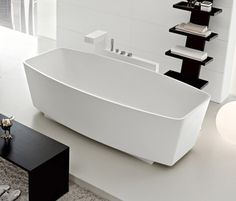 Modern style white bathtub mounted to a wall. The wall provides comfort as being a toiletry cupboard. The contrasting black and white theme of the bathroom also works well together.
