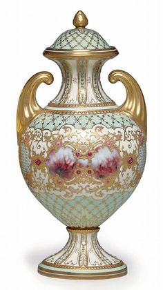 A COALPORT PORCELAIN 'JEWELED' PALE-BLUE AND WHITE GROUND VASE AND COVER Late 19th/20th century, green printed crowned mark, gilt pattern no. V.3994 and 35 Of baluster form with upright pistol handles, set front and back with a central faux-agate cartouche flanked by 'jeweled' trellis panels divided by 'topaz' gems and embossed gold panels, the fluted neck and socle molded with 'pearls' and stiff-leaf tips, the interior enriched with powdered gilt