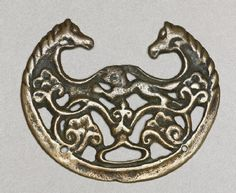 8th-9th century, Tibet, 'togchag' (amulet) representing horses, was used as a buckle, at the Ashmolean Museum (UK)