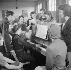 WORKERS WELFARE AT A ROYAL ORDNANCE FACTORY: LIFE AT ROF BRIDGEND, JANUARY 1942 ~ The YMCA Club leader leads a sing-song in the lounge of the war workers hostel at ROF Bridgend. The war workers and their Royal Air Force guest have gathered around the piano to join in the singing.