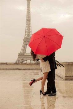 Couple qui s'embrasse sous la pluie devant la tour Eiffel