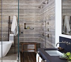 In the master bath, silver travertine was installed so its veins and patterns are contiguous, creating the appearance of a single slab of stone. The shower floor is teak, repurposed from the boardwalk at Coney Island.