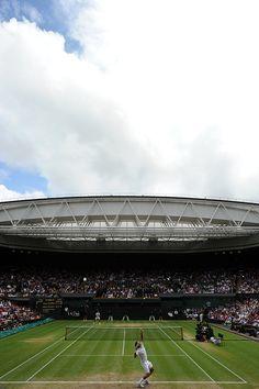 Roger Federer serves to Mikhail Youzhny on Centre Court during their quarter-final match. - Tom Lovelock/AELTC