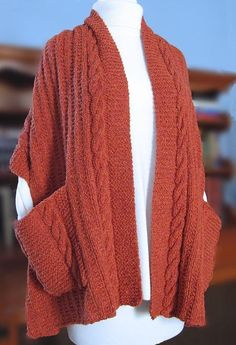 Curl up with this wrap, an e-reader, and a cup of cocoa for a relaxing evening at home. This wrap is worked in Aran weight yarn and features a simple cable running along the edges and featured on the pockets. Crochet Hooded Scarf, Knitted Poncho, Knitted Shawls, Crochet Scarves, Knit Crochet, Crochet Sweaters, Easy Scarf Knitting Patterns, Knit Vest Pattern, Shawl Patterns