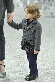 """No desfile Chanel Autunm/Winter 2012, um garotinho de 3 anos entrou de mão dada com uma modelo, vestido pela grife e carregando uma bolsa da coleção """" Boy Chanel """", fato que com certeza vai gerar uma certa polêmica!"""