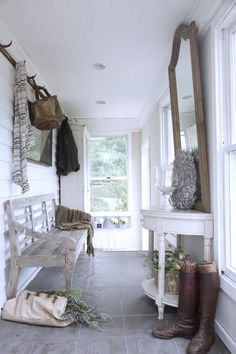 Half moon console, shabby bench, and slate tiles dress up a narrow cottage entryway