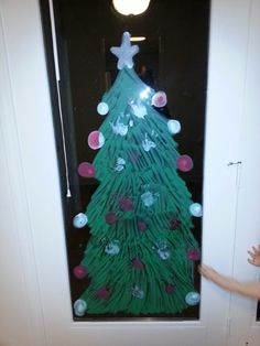 Christmas tree made with window chalk and the kids handprints as ornaments!  1. Outline your tree on a window and color it in 2. Paint your kids hands and/or feet with the window chalk and press it to your tree 3. Decorate it with whatever else you want 4. Walla: your own, personalized Christmas tree for the holidays!