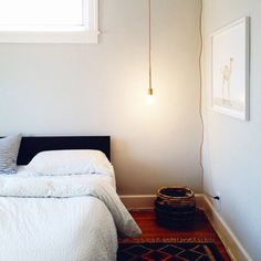 Sleek  white bedroom, wicker basket, moroccan rug