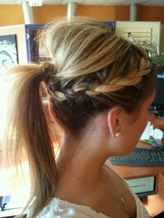 How to Recreate This Look (or something similar): 1. Tease the hair at your crown for volume and then clip it up out of the way of your work. 2. French braid the rest of your hair in two sections - braid horizontally from your temples, back towards the center of your head. Use hair ties to keep the braids in place for now. 3. Unclip the teased section of hair and smooth down to where the braids meet. Leave out a small section. Use an elastic to create a ponytail with all of the hair - you ca...