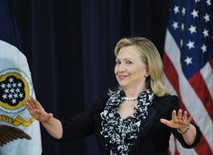 Secretary of State Hillary Clinton gestures for the audience to be seated before addressing the second annual Global Chiefs of Mission Conference March 13, 2012 in the Dean Acheson Auditorium of the State Department in Washington, DC.