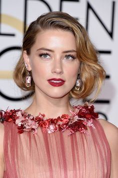January 10 2016 Amber Heard opted for Old Hollywood glamour, with curled hair worn in a faux bob, matt red lips and eyes defined with metallic shadow.