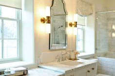 Stunning, classic bathroom design in white, with wall sconces. Discovered on search.porch.com #interiors #interiordesign