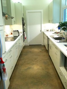 """Galley kitchen with ugly concrete floor which begs the question, """"Uh, what was so bad about linoleum"""""""