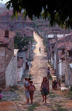 Children walk up a hill along a small street, Korce, Albania,