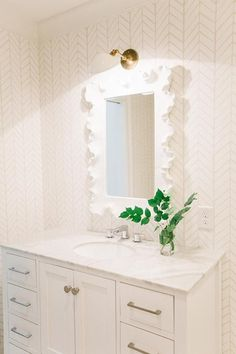 White bathroom features walls clad in Serena & Lily Feathers Wallpaper lined with a Ballard Designs Atoll Rectangular Mirror illuminated by a Schoolhouse Electric Newbury Sconce over a white vanity adorned with satin nickel hardware topped with white marble.