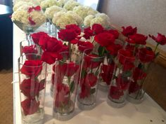 Red rose and white hydrangea centerpieces for a James Bond-themed event.