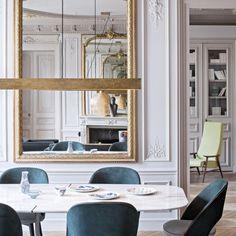 """Dans la salle à manger au miroir doré, au dessus de la table à manger en marbre, une suspension """"Blade"""", Baxter. Miroir d'origine et bibliothèque réalisée sur mesure par la société Renaissance et Restauration."""