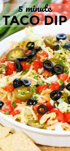 Taco Dip is the perfect game day appetizer, made with a creamy taco seasoned layer then topped with lettuce, tomatoes and cheese. Spice it up with jalapenos, black olives and green onions as well!#gameday #easyappetizer #nobakedip #homemade #makeaheadappetizer #creamydip