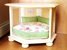 """Brighten up a hexagon-shaped dark wood end table with a fresh coat of paint and spruce up the inside to suggest a cute country doggie cottage, complete with a """"Home Sweet Home"""" sign. Fabric panels in a feminine print are Mod-Podged to the inside """"walls"""" and a comfy cushion and bolsters in a coordinating pattern make it perfect for a pet who likes a cozy sleeping corner. Get the tutorial at Playing With Scissors. - CountryLiving.com"""
