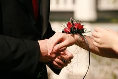 Teenage boy giving a girl a wrist corsage - Taliesin/Morguefile.com