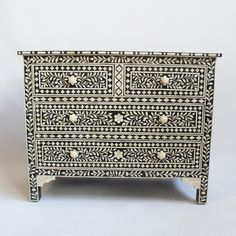 Beautiful intricate black and white traditional floral bone inlay patterns cover this four drawer dresser.  Each small piece is hand carved and then ground filled with charcoal black resin.