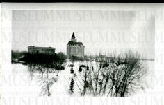 Image of the Bessborough Hotel in Saskatoon in winter - trees in foreground - church and bridge visible to right in background