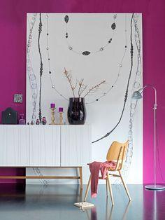 Een bijzondere blikvanger in de kamer is deze uitvergrote illustratie van een aantal sierlijke kettingen, minstens zo mooi als een schilderij aan de wand.