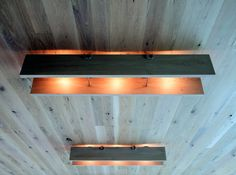 Simple ceiling light of two wooden boards and three bulbs.